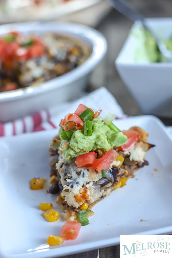 Slice of taco pie with ground beef, beans, pepper, and corn with cheese and baked in a pie crust and topped with guacamole and tomatoes on a white plate and a tan an red napkin with taco pie in the and bowl of guacamole in the background.