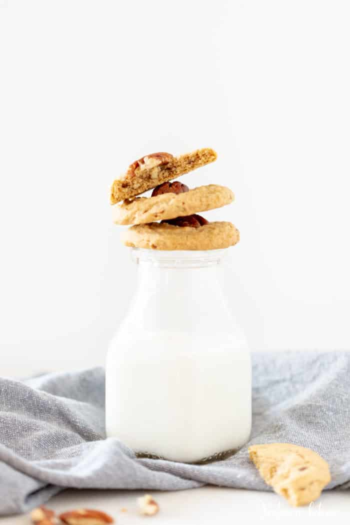 3 pecan and brown sugar cookies stacked on a glass of milk resting on a towel