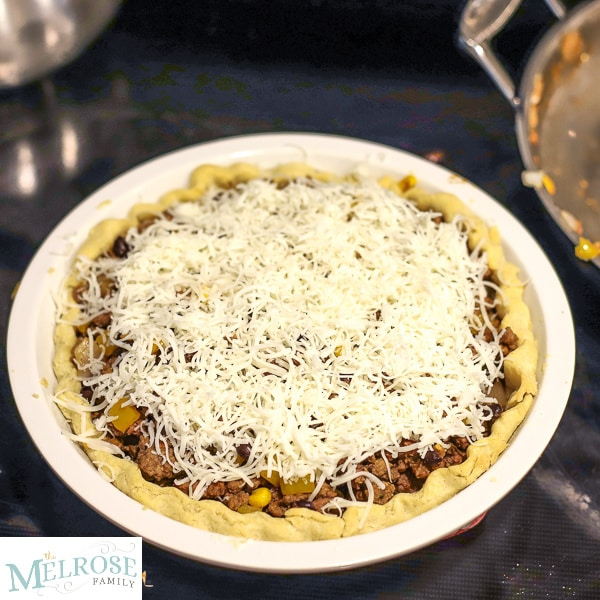 Pie shell with taco filling and covered in cheese on top of the stove.