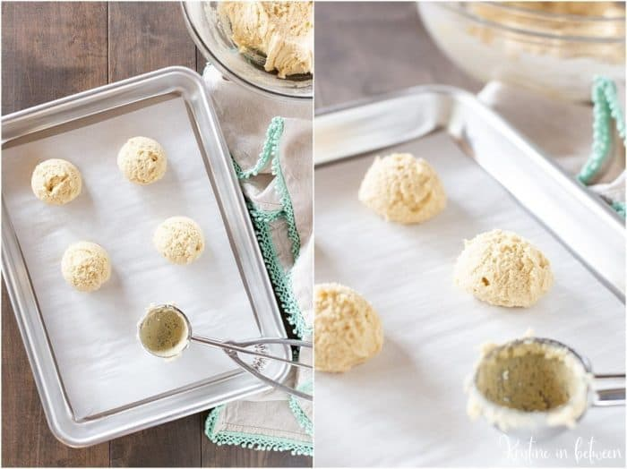 Soft sugar cookie dough scooped on a parchment cookie sheet with the cookie dough behind it.
