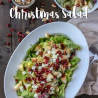large white oval dish filled with Christmas salad on wooden table with a brown napkin and forks to the right and nuts, pomagranate seeds and a smaller salad behind it.