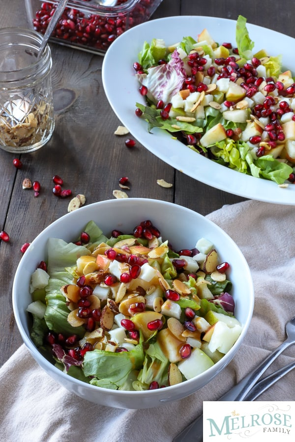 bowl of christmas salad with lettuces, candied almonds, pears, apples, cheese, and pomegranate seeds in a white bowl on a brown napkin with a larger bowl of holiday salad behind it.