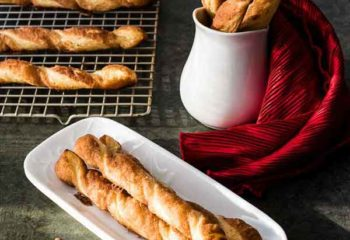 cinnamon twists laying on a white platter with more cinnamon twists behind it in a white vase and laying on a baking rack