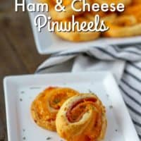 two ham and cheese pinwheels on a whilte plate with more pinwheels behind