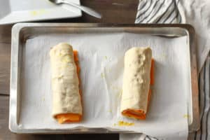 ham and cheese pinwheels rolled up on a baking sheet