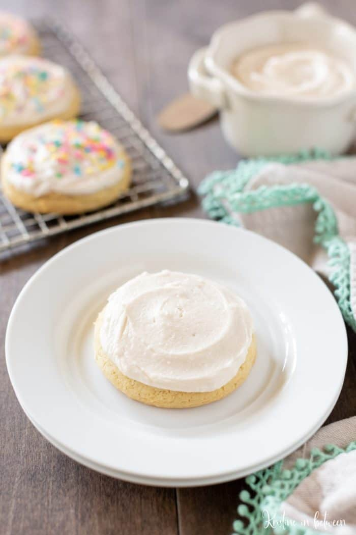 Soft sugar cookie with white buttercream frosting on a white place with a teal napkin and decorated sugar cookies behind it