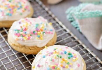 3 sugar cookies with buttercream frosting with sprinkles on a wire rack with a napkin and bowl of frosting behind