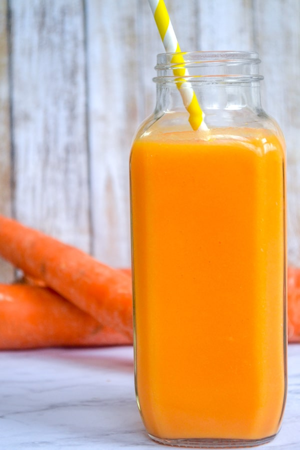 orange carrot smoothie in a bottle with yellow straw and carrots behind it