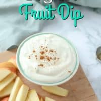yogurt fruit dip sprinkled with cinnamon in a turquoise bowl on a wood cutting board with apples behind it