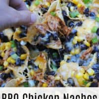 Hand taking BBQ chicken nachos with chicken, beans, corn, jalapenos, and cheese