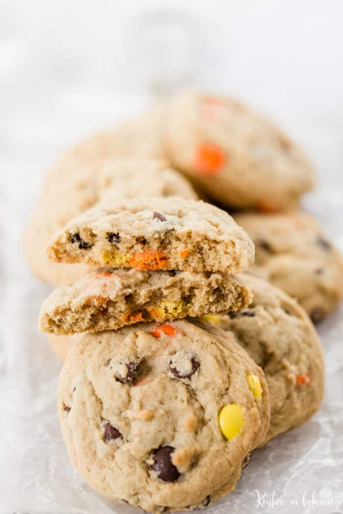 reeses peanut butter cookies in a pile with a cookie broken in half on top