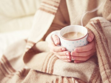 woman wrapped in a quilt blanket holding coffee