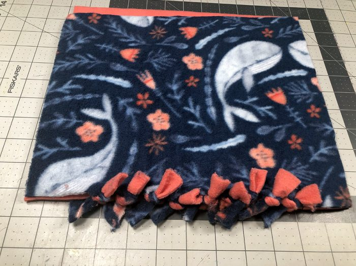Finished front side of double-knotted fabric laying on cutting mat