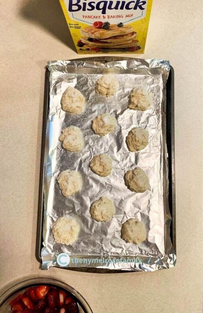 1 dozen shortcake bisquits on a foil-lined baking sheet