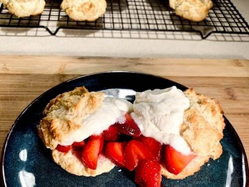 Strawberry Bisquick shortcakes on a plate topped with whipped cream and shortcakes on a cooling rack behind it