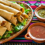 several flautas on a serving tray with green and red salsa