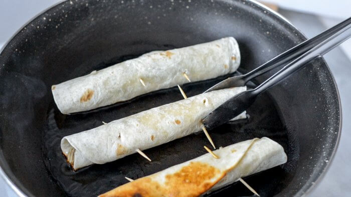 Three Chicken Flautas in a frying pan with tongs