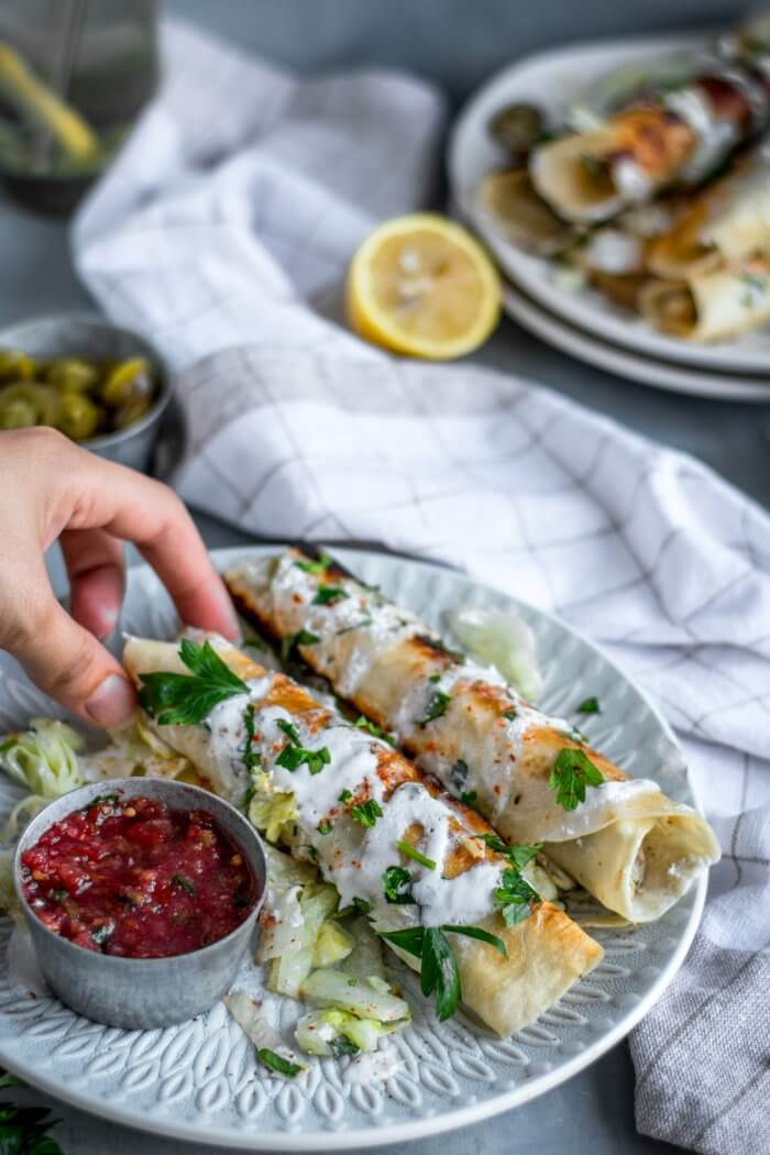 Hand reaching for a chicken flauta on a plate of two with salsa dipping sauce