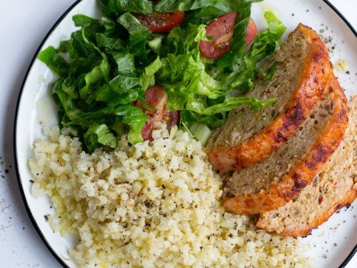 Turkey keto meatloaf on a plate with salad and rice