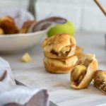 apple pie bites split in half with two stacked behind it