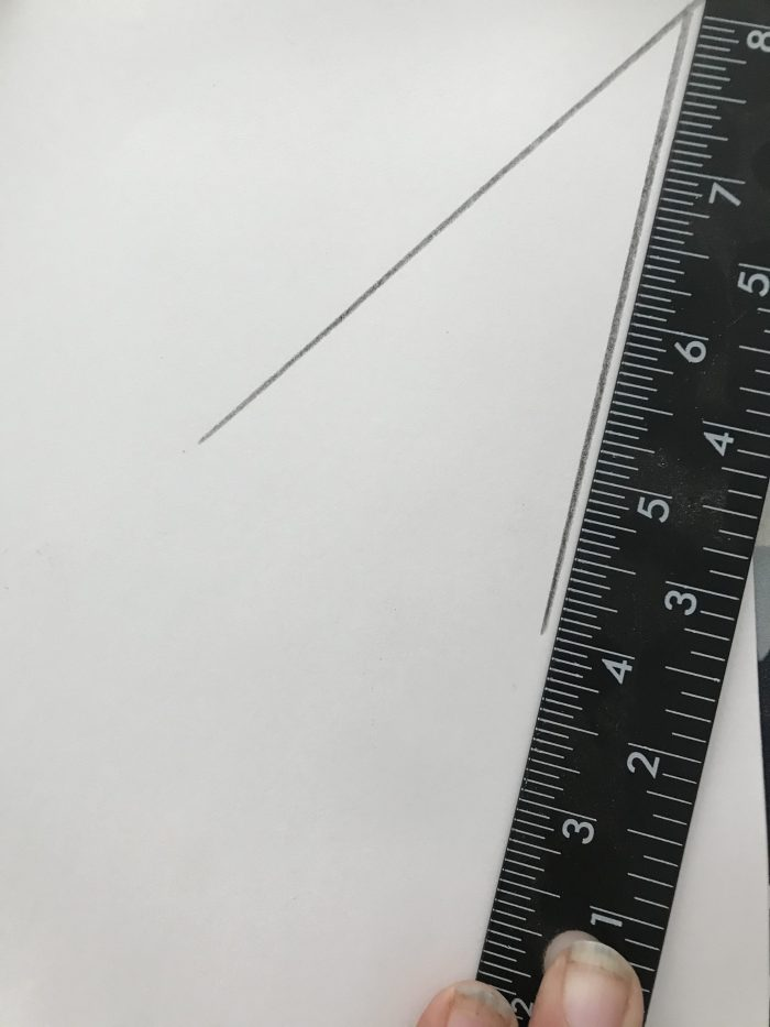 2 diagonal lines drawn in a corner on a piece of paper with scale