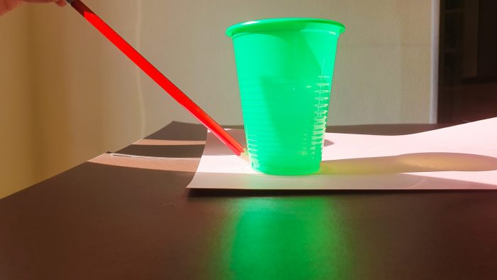 drawing a circle on paper using a plastic cup and a pencil