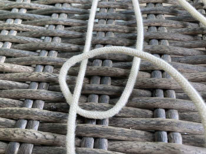 loop formed using macramé cord with a piece of macramé string in the middle