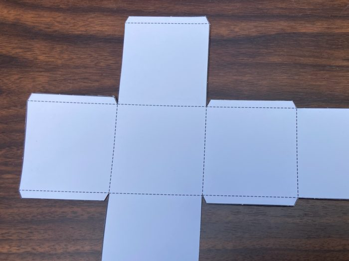 gift box template with solid and dotted lines placed on a surface