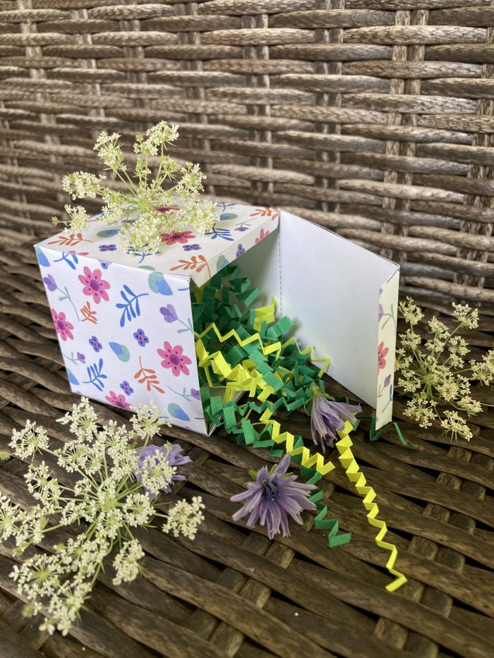 gift box filled with  colorful shredded paper and flowers placed beside