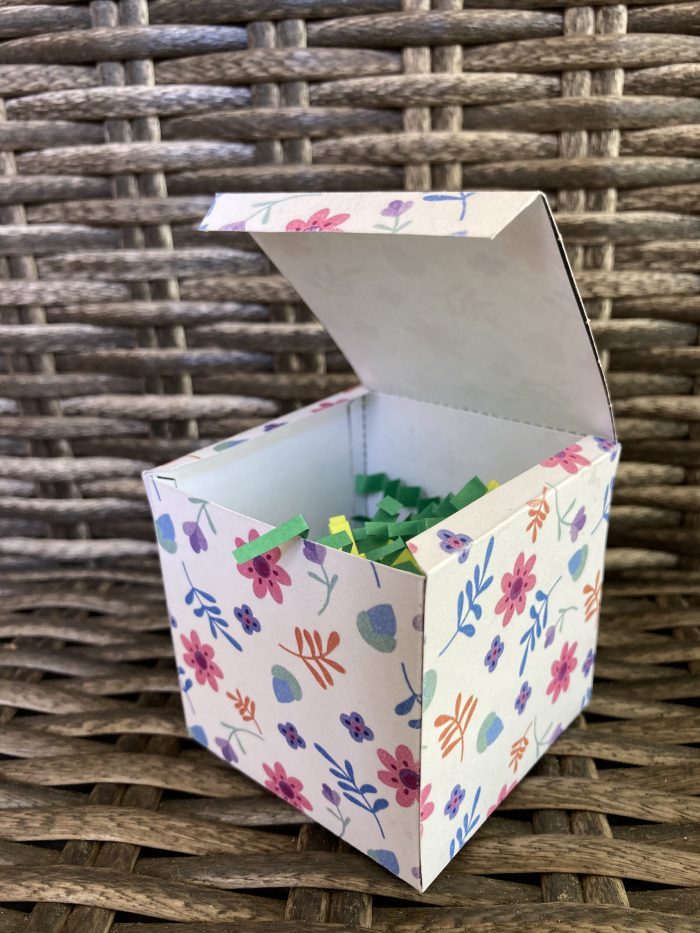 gift box with lid open and  colorful shredded paper placed inside