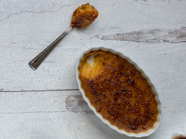 creme brulee in ramekin with a spoon placed beside